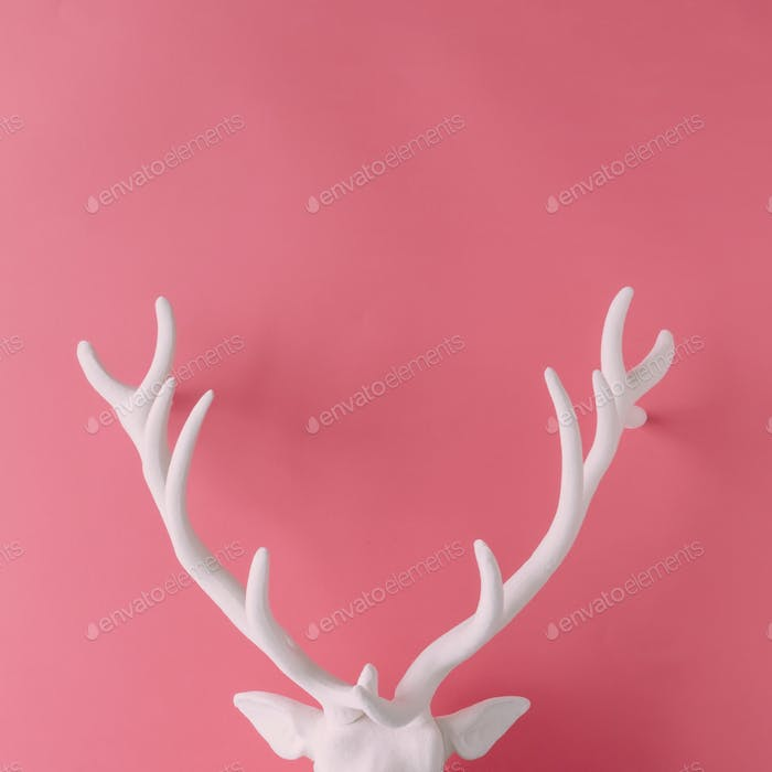 White Christmas reindeer head with antlers on pink hipster background. Flat lay. New Year concept.