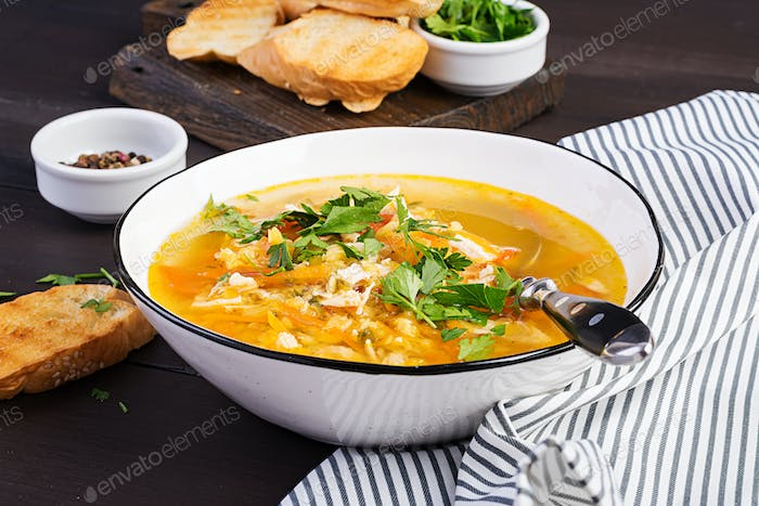 Red lentil soup with chicken meat and vegetables close-up on the table. Healthy food.