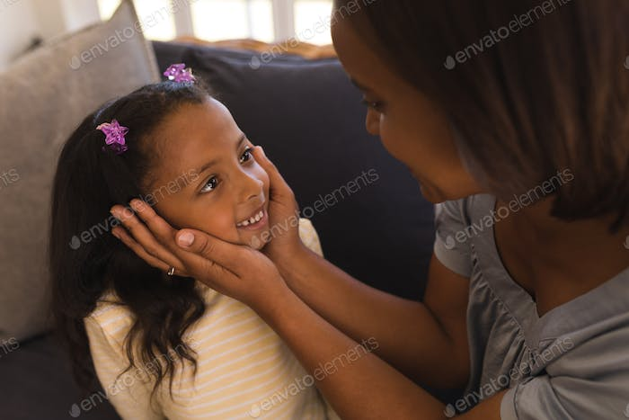 Close-up of mother and daughter looking at each other in living room at home
