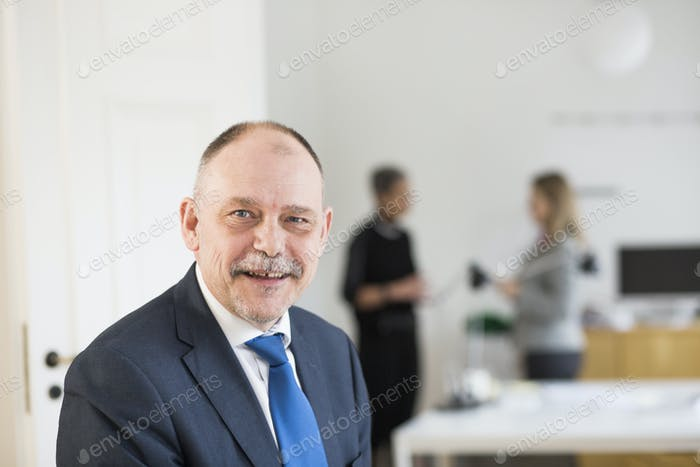 Portrait of confident businessman smiling while colleagues discussing in background at office