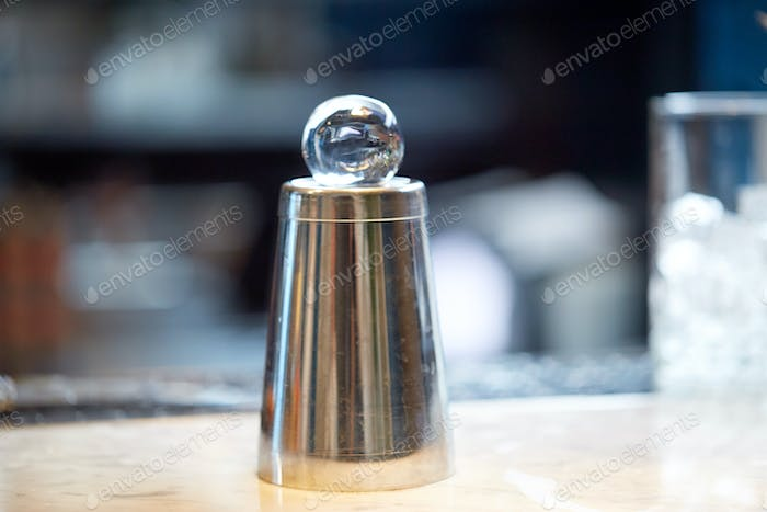 hand-cut ice ball on top of cocktail shaker at bar