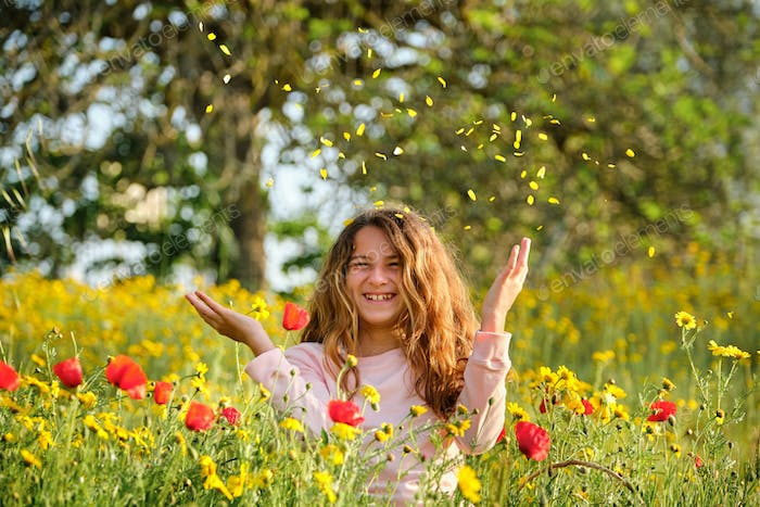 Delighted girl throwing petals in air