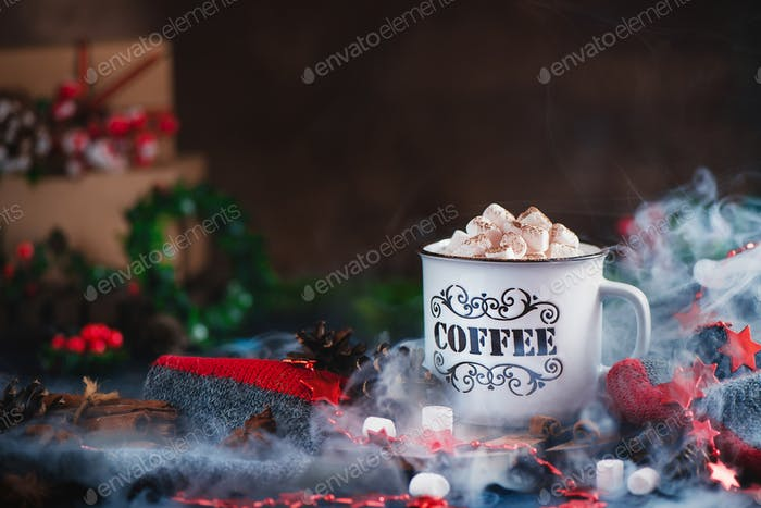 Hot chocolate with marshmallows in a cozy enamel mug with steam and Christmas decorations