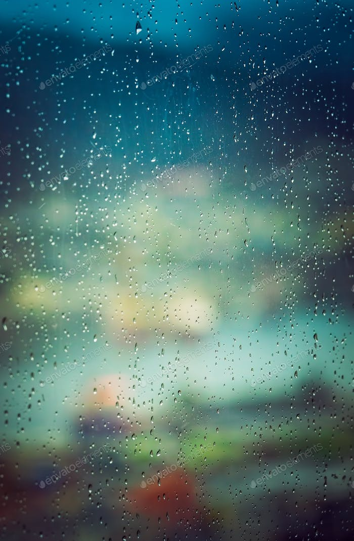 Defocused city colors seen through the wet window