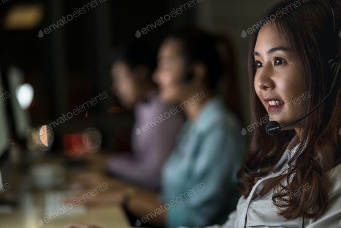 Portrait of Asian Female customer care service with business man smiling and working hard late
