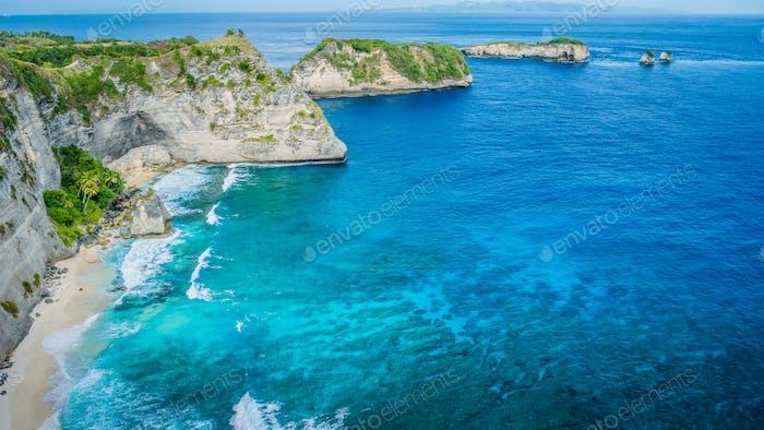 Coastline with rocky edge facing ocean behind at Atuh beach on Nusa Penida island, Indonesia