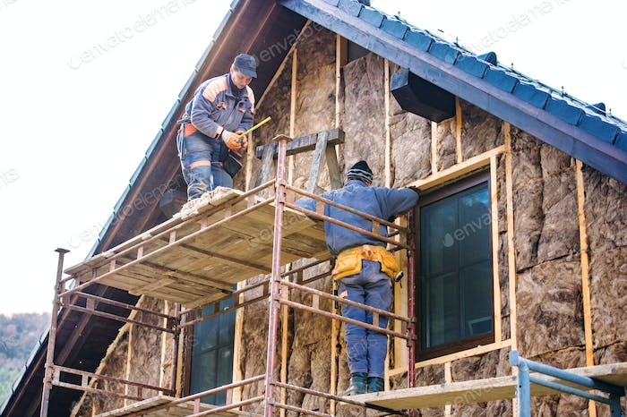 Construction workers thermally insulating house facade with glass wool.
