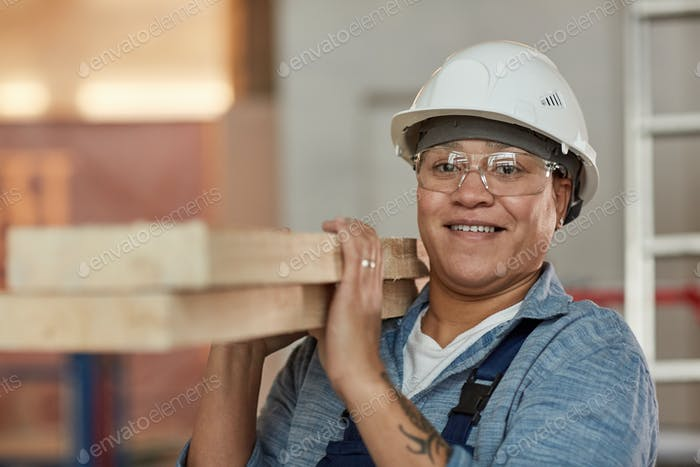 Smiling Woman Carrying Wood Boards at Construction Site