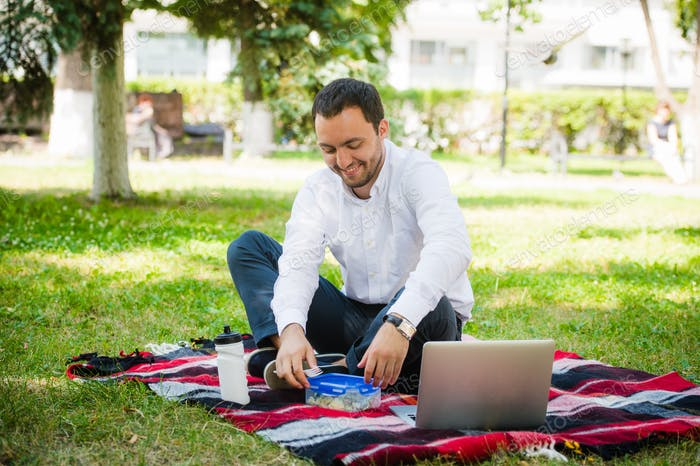 Businessman working in the garden and eating lunch