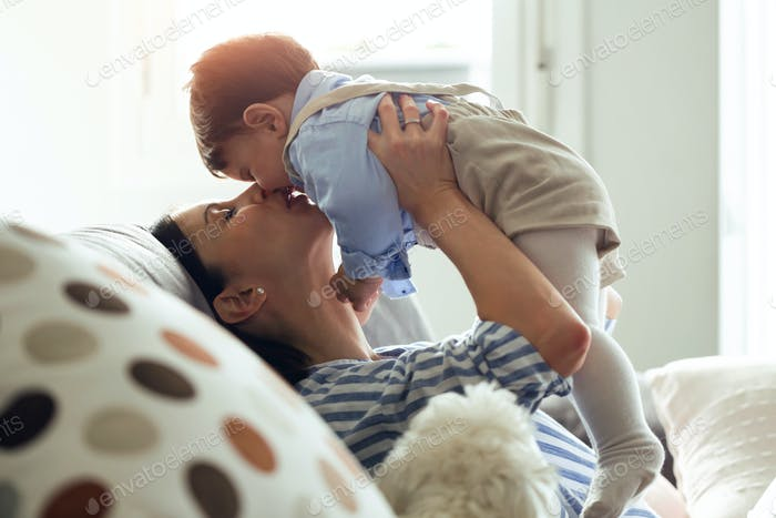 Pretty young mother with her baby playing and loving in the living room at home.