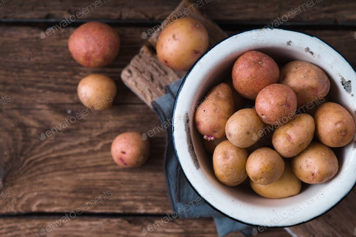 Raw potatoes in a white bowl on a napkin copy spase