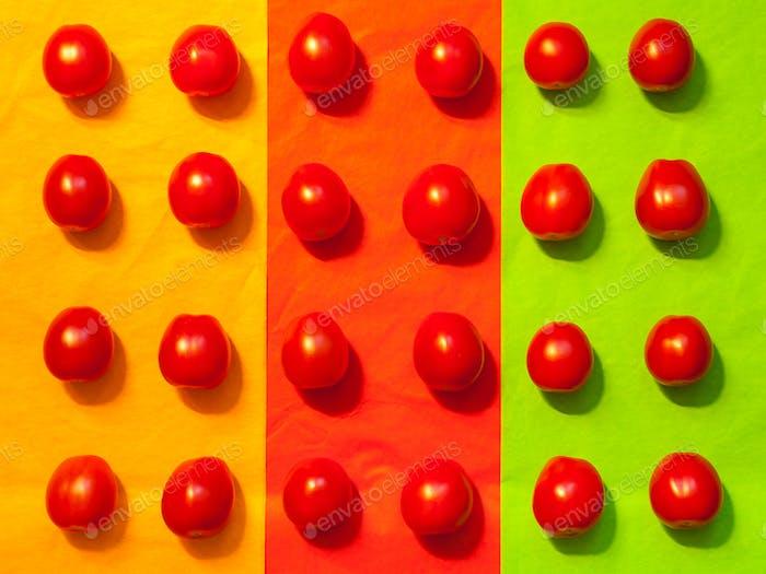 Saftige Tomaten auf einem farbigen Papierhintergrund
