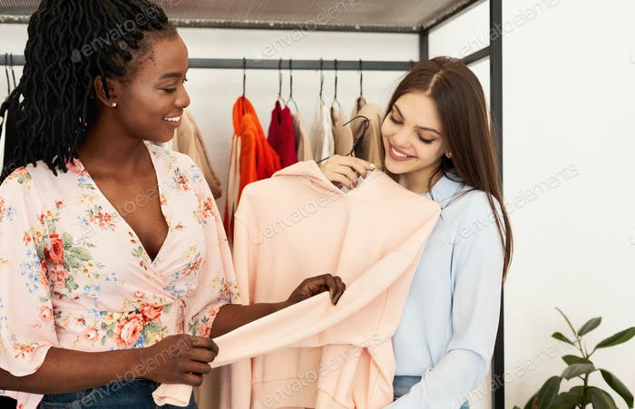Personal Stylist Picking Seasonal Updates For Client's Wardrobe In Showroom