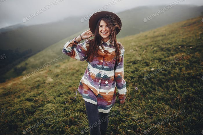 girl traveler holding hat and looking at mountains