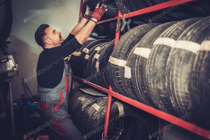 Professionelle Automechaniker die Wahl neuer Reifen in Auto-Reparatur-Service.