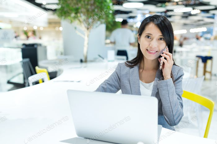 Businesswoman talk to cellphone with her laptop computer