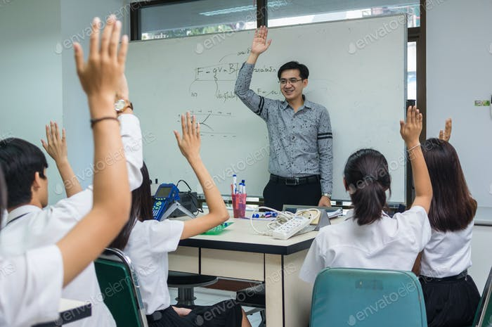 Asian teacher Giving Lesson over the the physics formular on white board in science laboratory