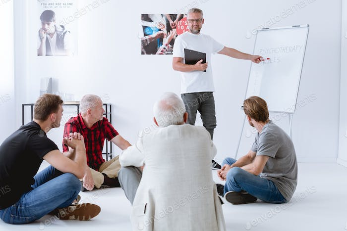Man standing in front of a group during psychotherapy session
