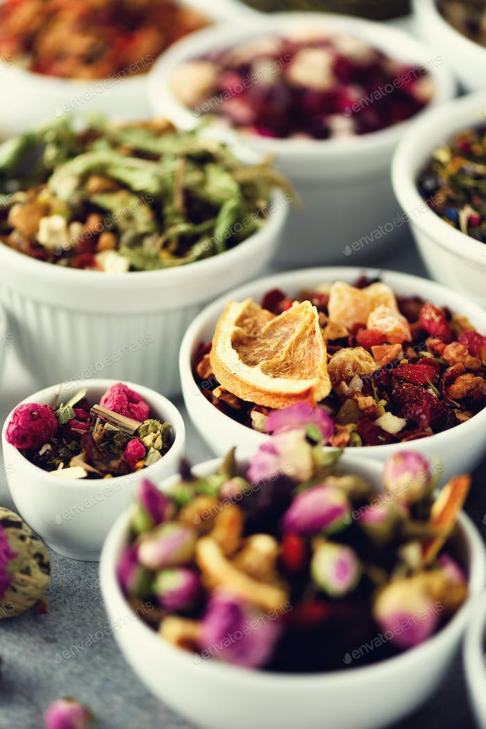 Assortment of dry tea in white bowls. Tea types backgound: green, black, floral, herbal, mint