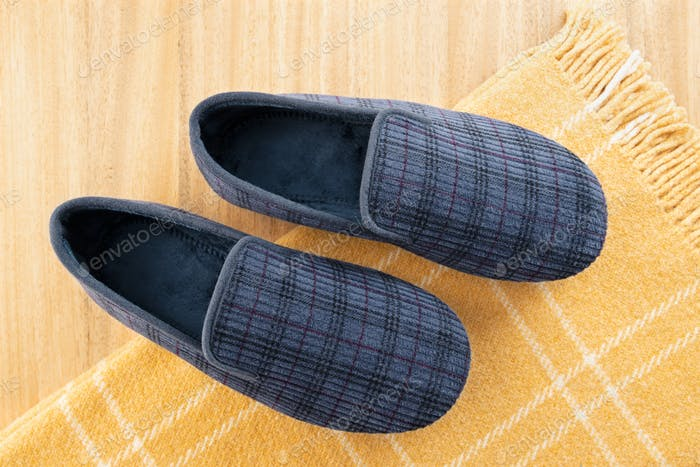 Male home slippers and wool blanket on table