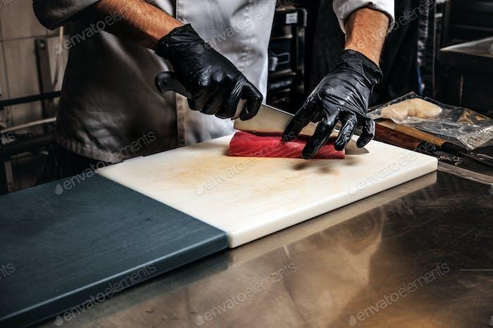 Крупным планом фото повара в форме и перчатках, готовящего суши на разделочной доске на кухне.