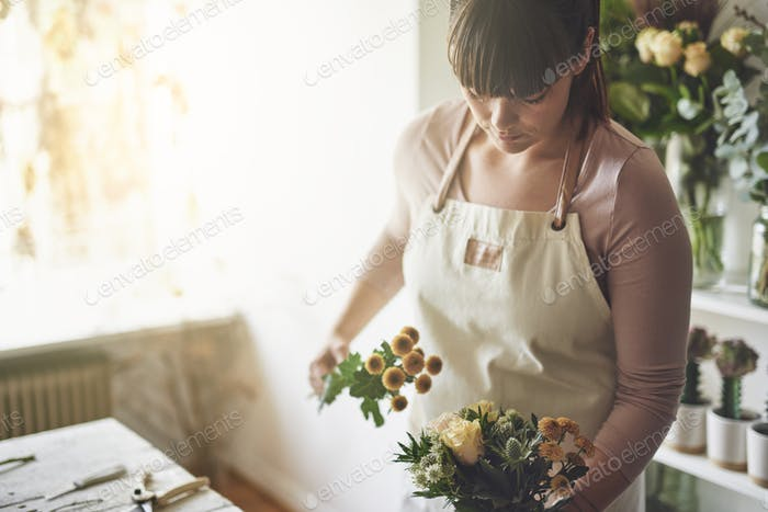 Young florist making a bouquet in her flower shop