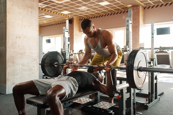 Man and his trainer doing exercise with barbell