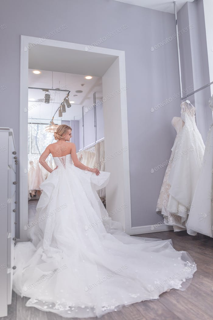 Attractive bride in a white dress in the store