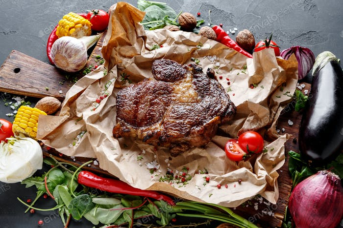 Rib eye steak on cooking paper, parchment with vegetables border on dark background