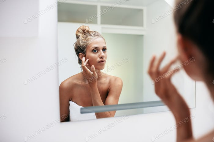 Female in bathroom looking into the mirror