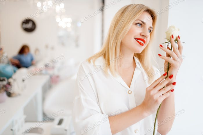 Woman holds rose, focus on manicure and flower