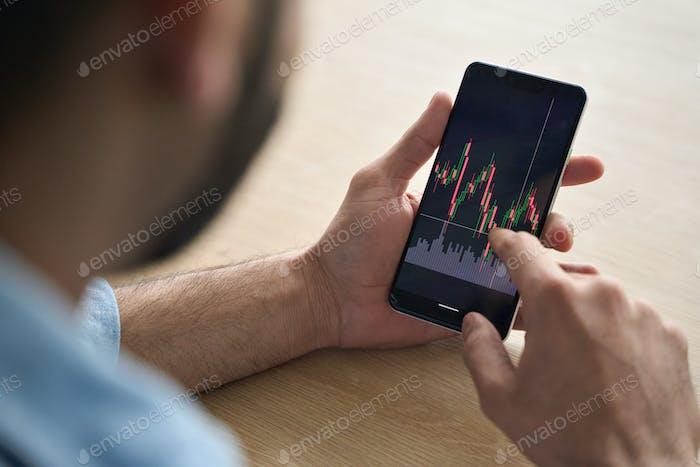 Las manos del corredor de cerca sosteniendo el teléfono móvil con bolsa de valores y gráficos.
