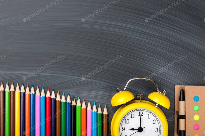 Colorful pencils, alarm clock and notepad on blackboard