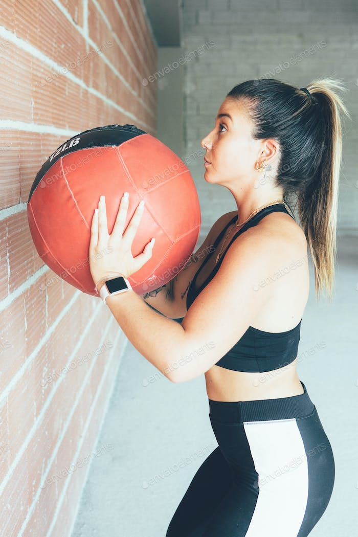 Concentrated_fit_woman_doing_wall_ball_routine