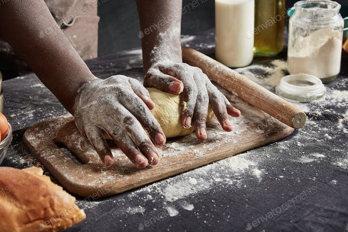 Indoor shot of black man with dirty hands kneads pasrty or dough carefully, uses rolling pin, prepar