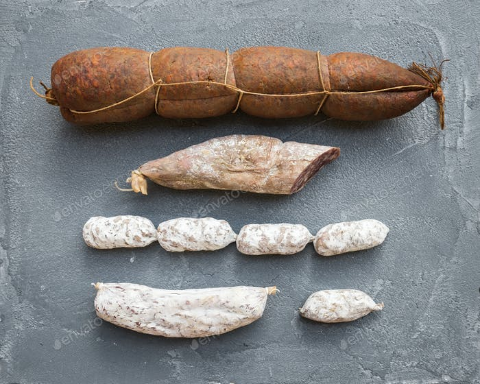 Italian salami sausages of different kinds over a rough grey concrete background