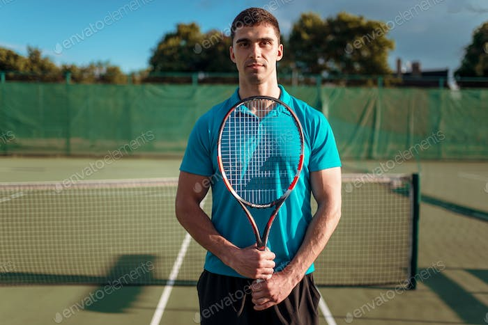Athletic male tennis player plays on outdoor court
