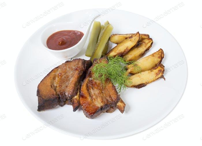 Schweinerippchen mit Kartoffeln und Gurken gebraten.