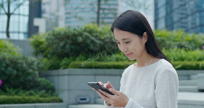 Woman sending sms on cellphone at outdoor
