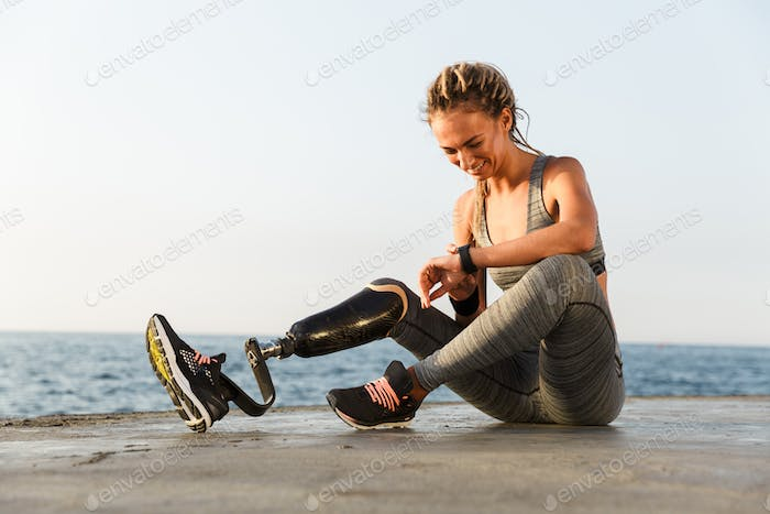 Smiling disabled athlete woman with prosthetic leg