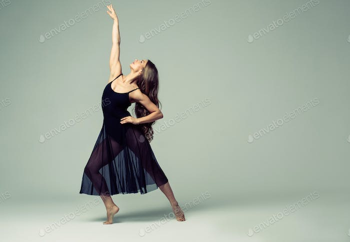 Ballet dancer woman black dress on gray background.