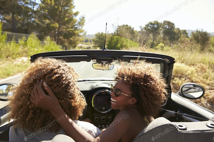 Woman embraces her partner as he drives, rear passenger POV