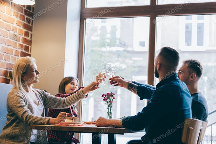 Four friends sitting together with glasses of champagne.