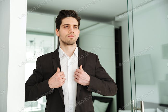 Serious young businessman standing in home