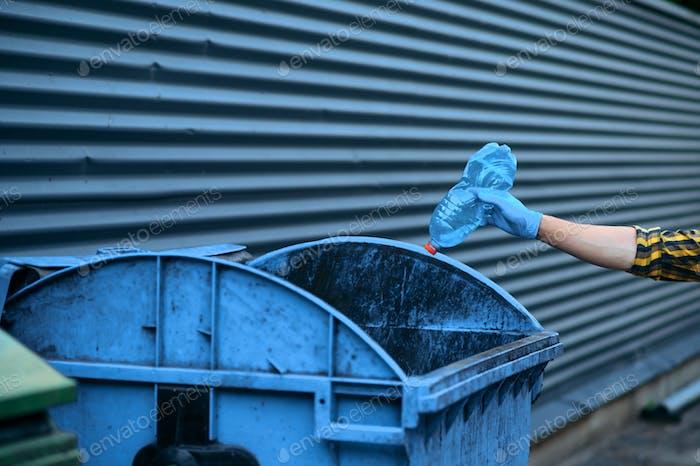 Volunteer puts trash into the can, volunteering