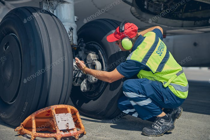 Focused professional male technician checking the undercarriage