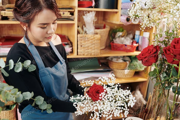 Young woman arranging flowers in bouquet