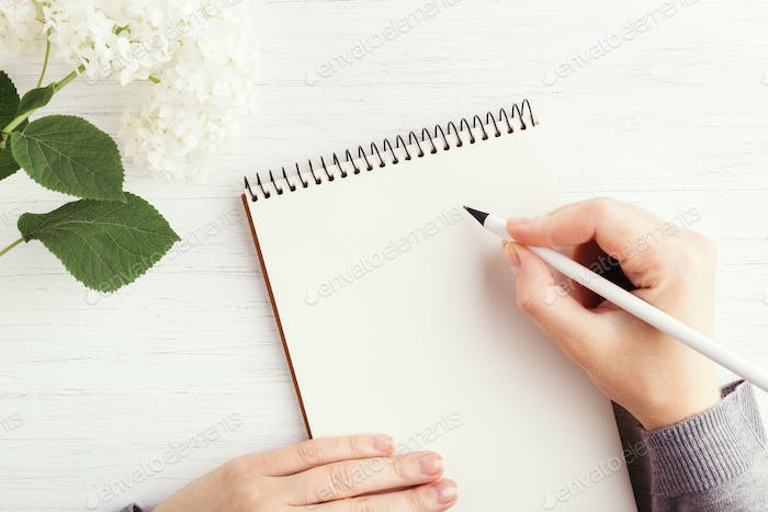 Female`s Hands Writting in Notebook.