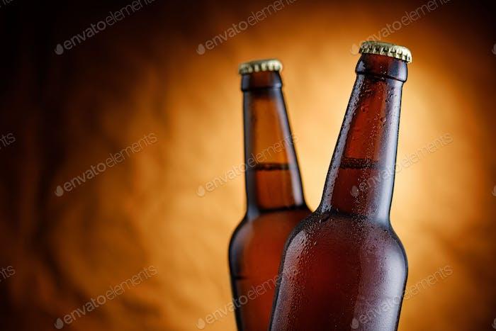 Two sealed unlabelled bottles of cold beer