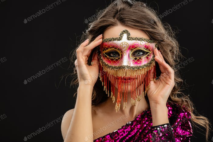 Beautiful woman wearing venetian carnival mask against black background. Holds hands near face